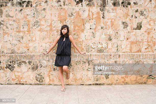 Woman leaning against a wall of a castle, Morro Castle, San Juan, Puerto Rico, USA