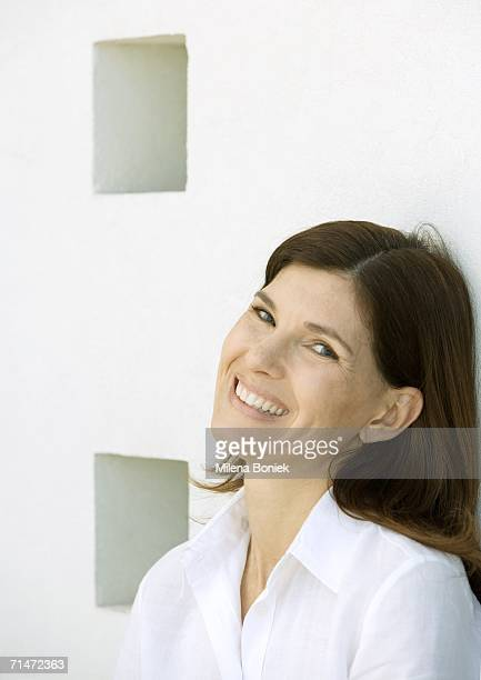 woman leaning against a wall, smiling and looking at camera, portrait, close-up - head back stock pictures, royalty-free photos & images