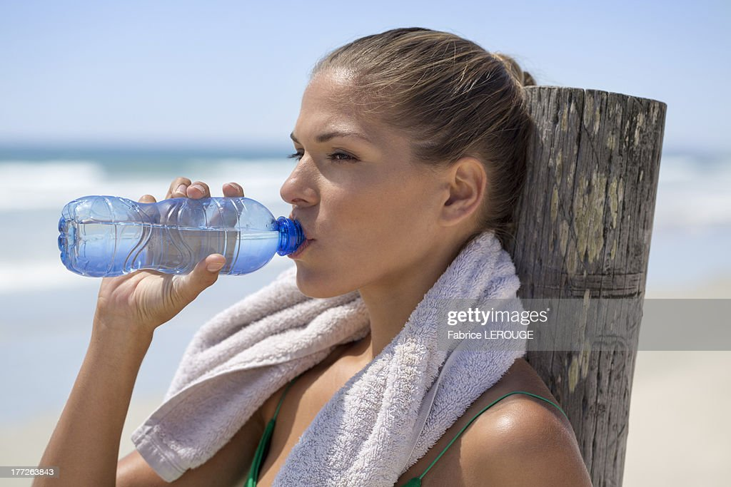 Woman leaning against a wooden post on the beach drinking water : Stock Photo