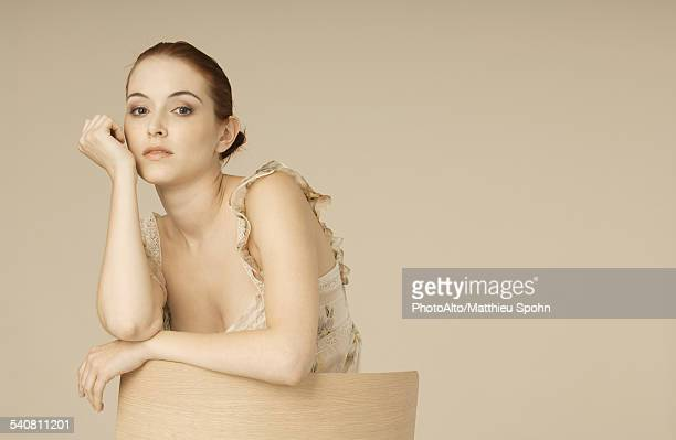 woman leaning against back of chair, portrait - kin in de hand stockfoto's en -beelden