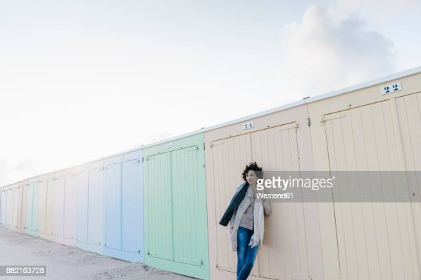 Woman leaning against beach hut