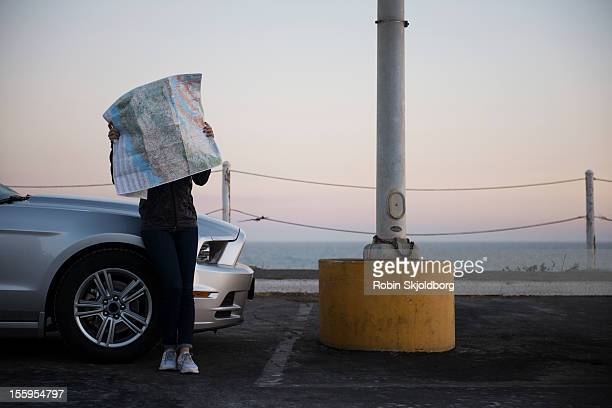 Woman leaning against car and looking at map