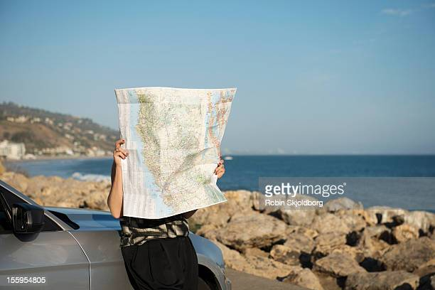 Woman leaning against car looking at map