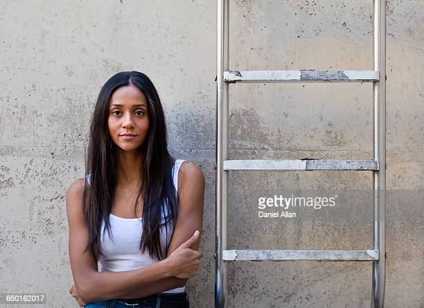 Woman leaning against concrete wall next to ladder, arms crossed looking at camera