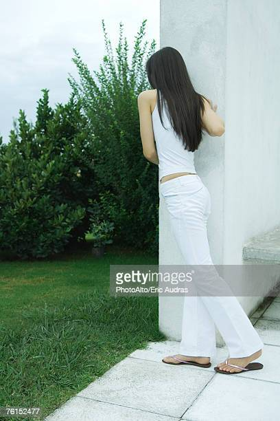 """""""Woman leaning against corner of wall, rear view, full length"""""""