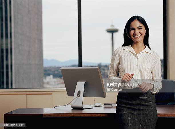 Woman leaning against desk in office, smiling, portrait