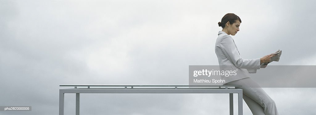 Woman leaning against edge of table, holding newspaper, side view, in front of overcast sky : Stockfoto