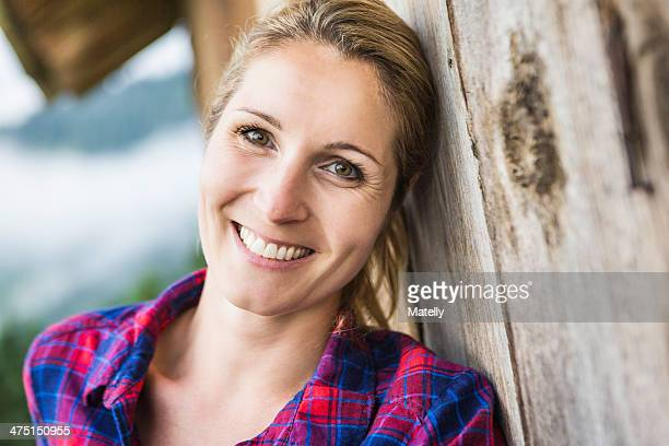 Woman leaning against exterior wall of wooden shack