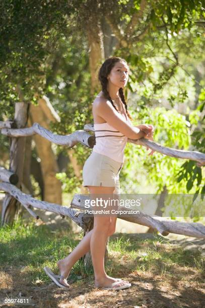 Woman leaning against forest fence