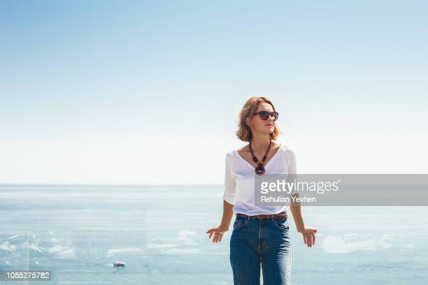 woman leaning against glass balcony on seaside terrace - frau bluse durchsichtig stock-fotos und bilder