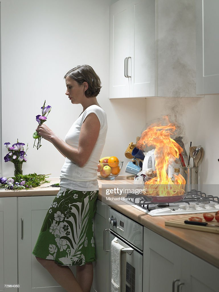 """Woman leaning against kitchen worktop holding flower, frying pan on fire behind"" : Stock Photo"