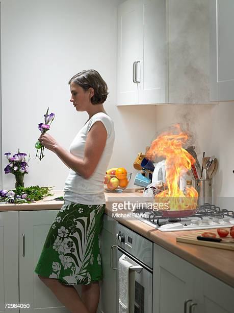 """woman leaning against kitchen worktop holding flower, frying pan on fire behind"" - pericolo foto e immagini stock"