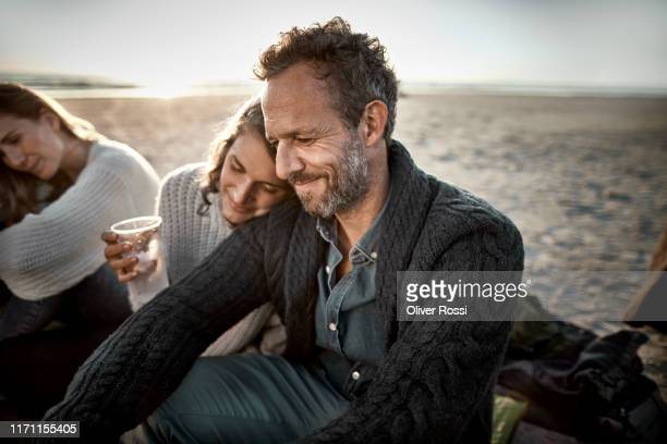 woman leaning against man's shoulder on the beach at sunset - leisure activity stock pictures, royalty-free photos & images