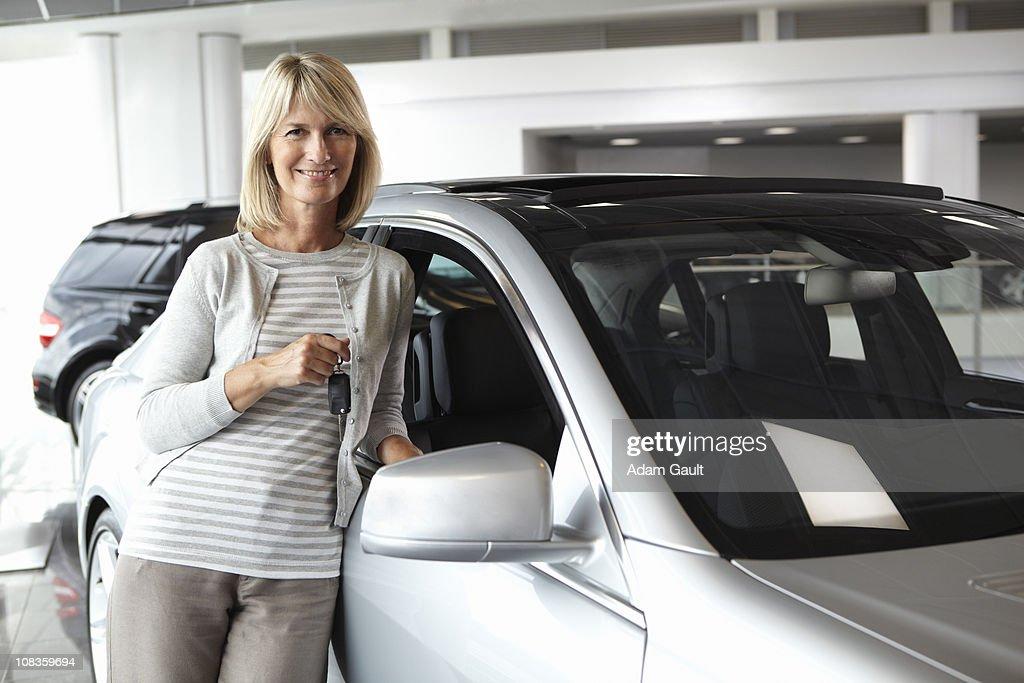 Woman leaning against new car in showroom : Bildbanksbilder