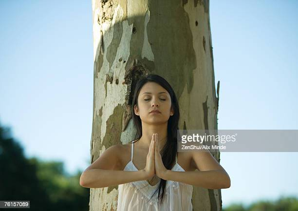 Woman leaning against tree, doing yoga pose