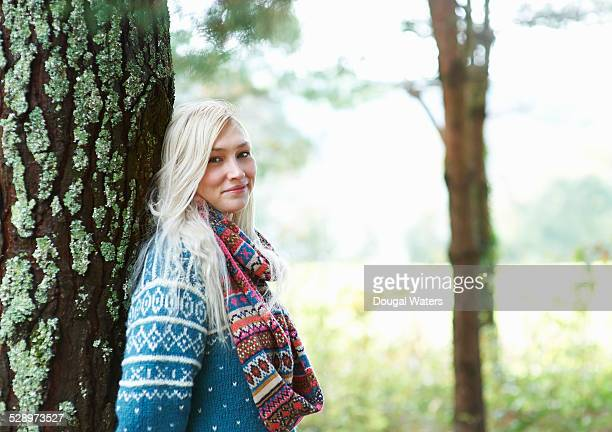 Woman leaning against tree in countryside.