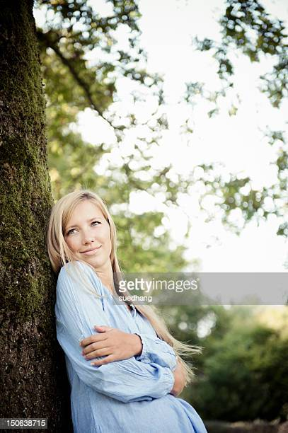 Woman leaning against tree in park