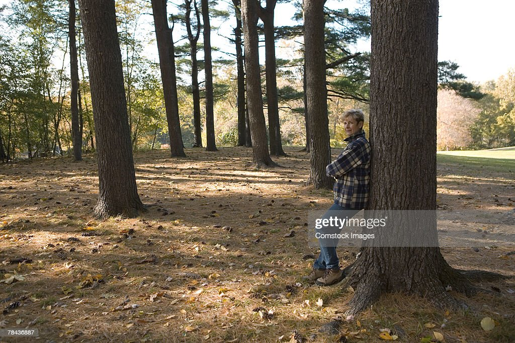 Woman leaning against tree : Stockfoto