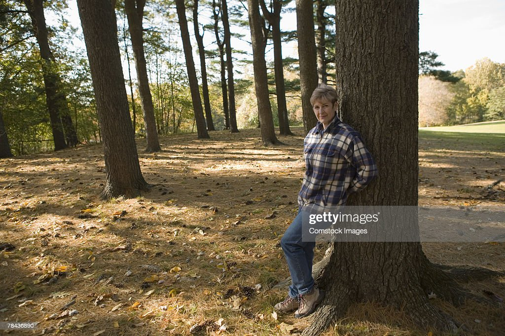 Woman leaning against tree : Foto de stock