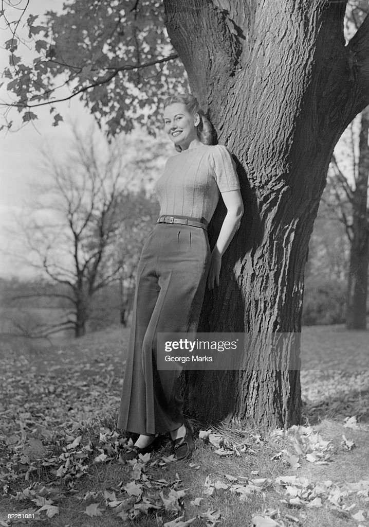 Woman leaning against tree, portrait : Stock Photo