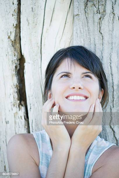 Woman leaning against tree trunk, looking up and smiling hopefully