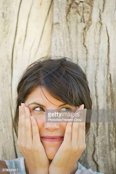 Woman leaning against tree trunk, smiling and holding face in hands, portrait