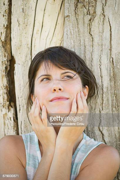 woman leaning against tree trunk with face in hands, looking up dreamily - wishful skin stock pictures, royalty-free photos & images