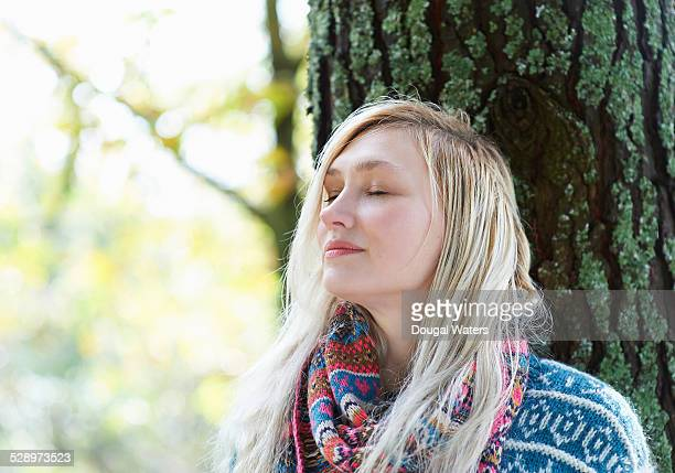 Woman leaning against tree with eyes closed.