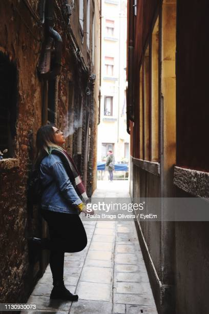 woman leaning against wall and smoking while standing in alley - one young woman only stock pictures, royalty-free photos & images