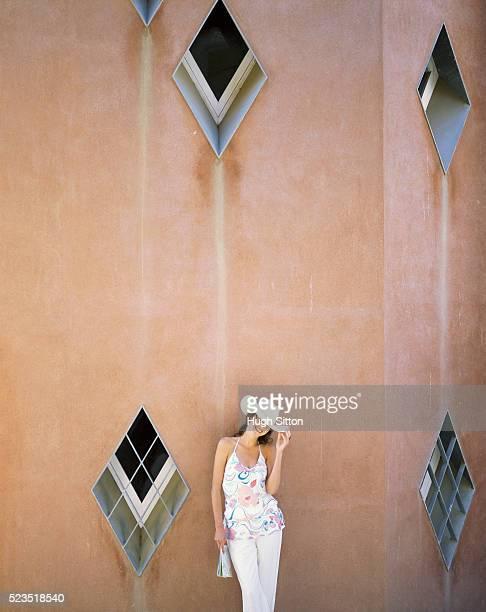 woman leaning against wall in park guell - hugh sitton stockfoto's en -beelden