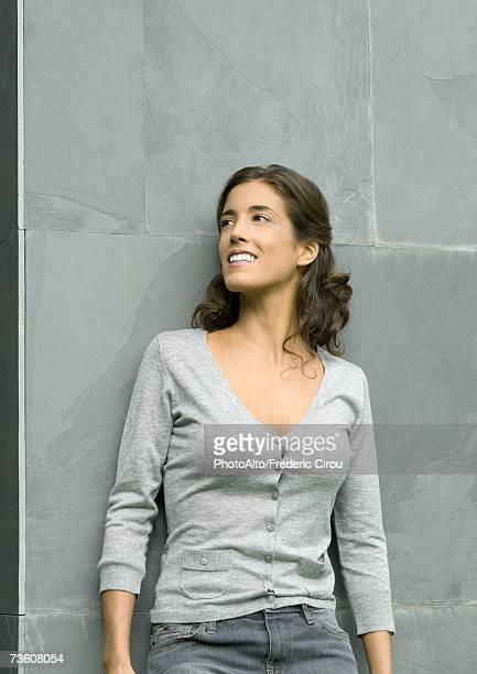 woman leaning against wall, smiling, portrait - v neck stock pictures, royalty-free photos & images