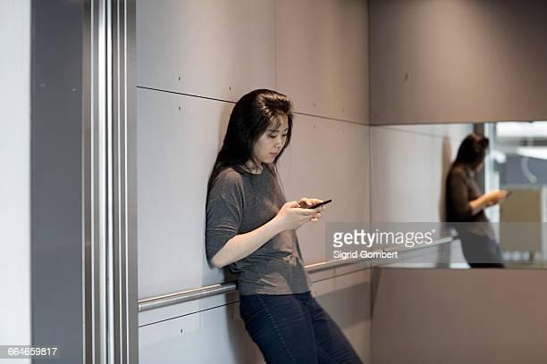 woman leaning against wall, using smartphone - sigrid gombert stock-fotos und bilder