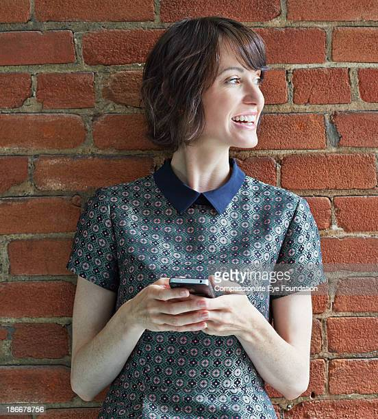 Woman leaning against wall with mobile phone