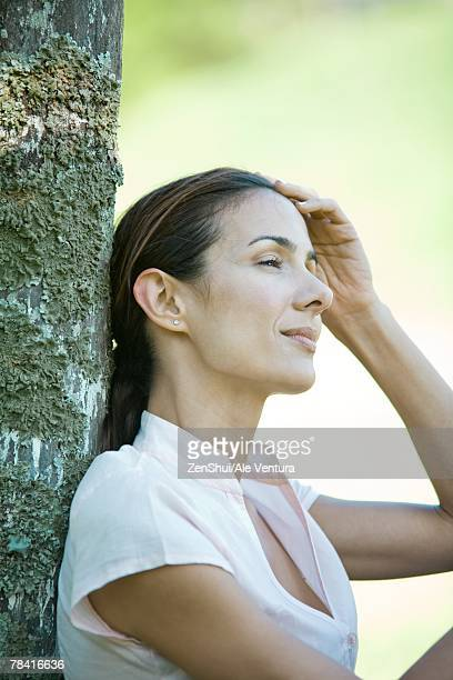 Woman leaning against wooden post, looking away, head and shoulders