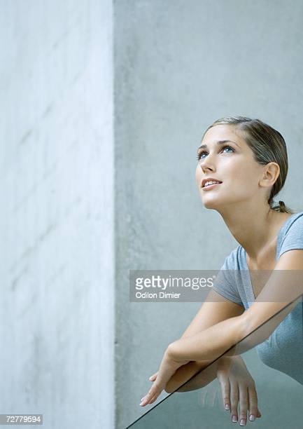 Woman leaning arms on balcony, looking up