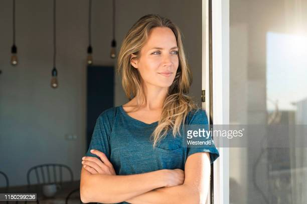 woman leaning at open window at home looking sideways - beschaulichkeit stock-fotos und bilder