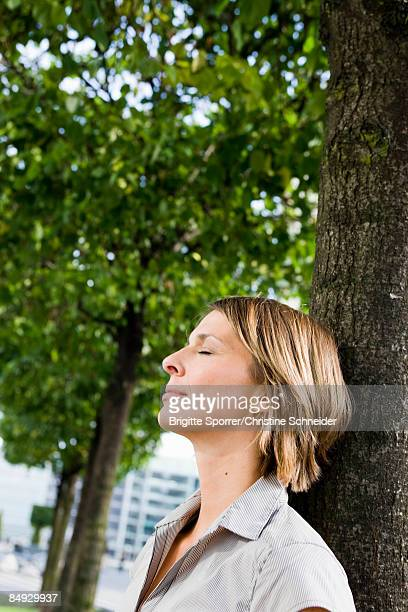 Woman leaning at tree