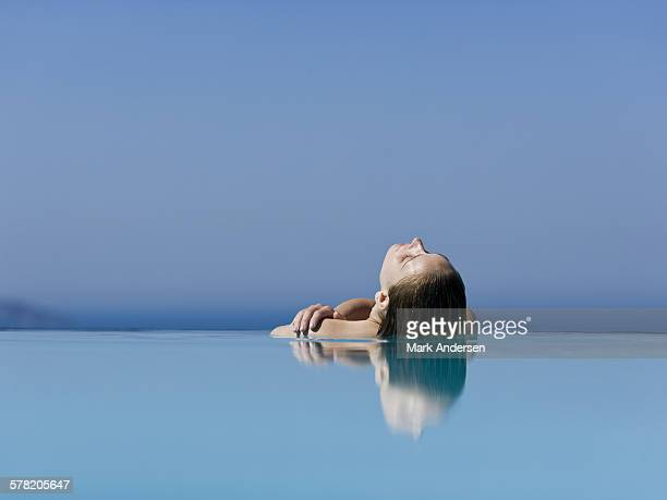 Woman leaning back in outdoor pool reflection