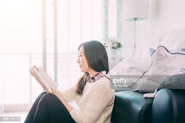 woman leaning by the sofa reading books relaxingly - yiu yu hoi stock pictures, royalty-free photos & images