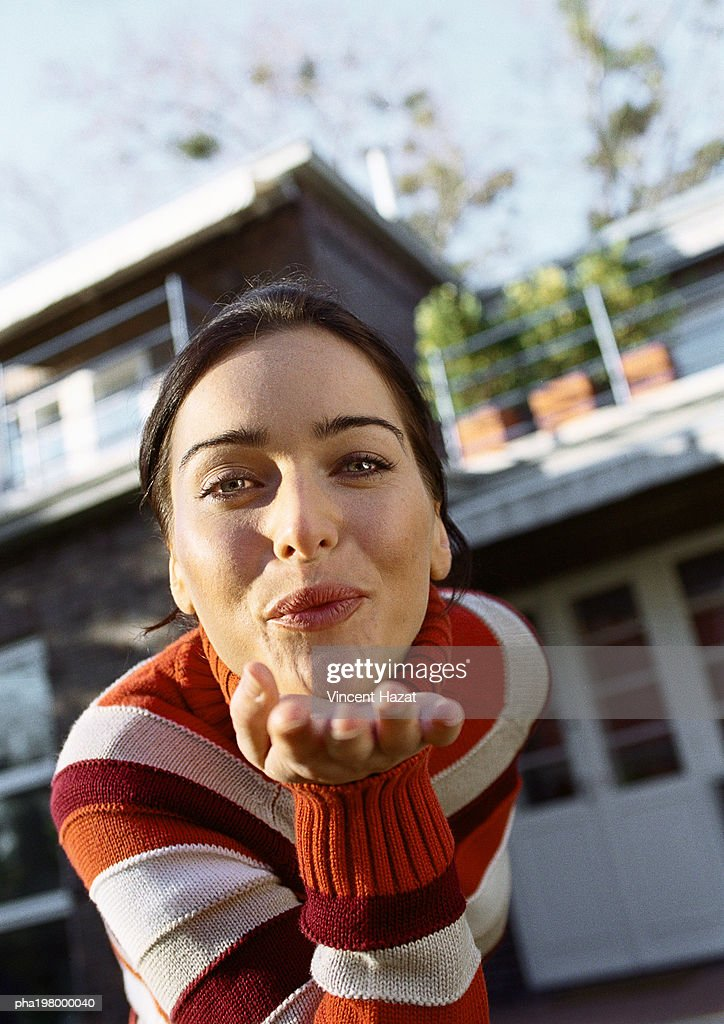 Woman leaning forward blowing a kiss, head and shoulders, close-up, house in background, low angle view : Stockfoto