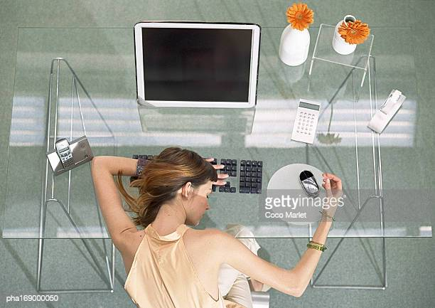 Woman leaning head on desk with futuristic devices, high angle view