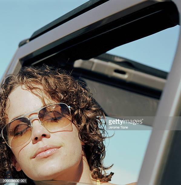 Woman leaning head out window of 4X4, wearing sunglasses, close-up