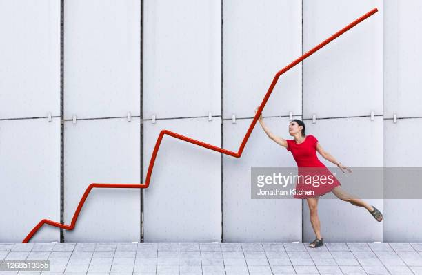 woman leaning holding up graph - moving up stock pictures, royalty-free photos & images