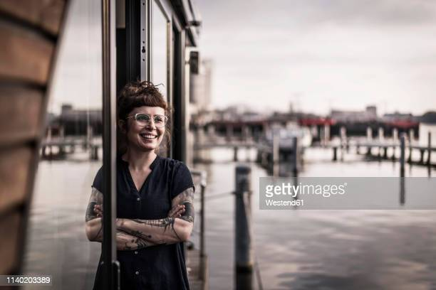 woman leaning in window of a houseboat, taking a break - houseboat stock pictures, royalty-free photos & images