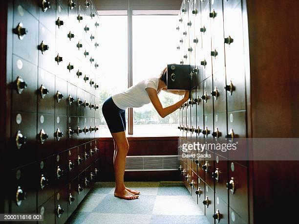 Woman leaning into locker