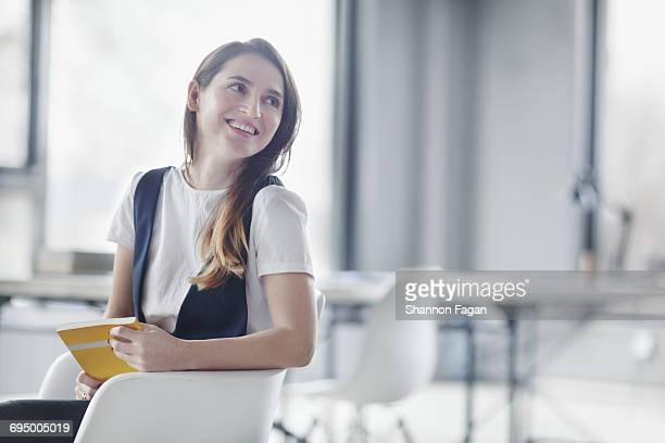 Woman leaning looking sideways in office studio