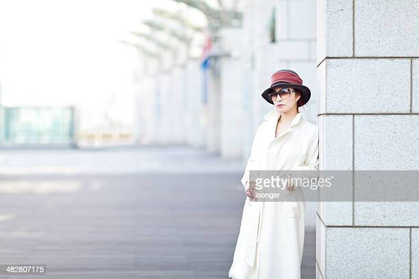 woman leaning on a shopping mall column - overcoat stock pictures, royalty-free photos & images