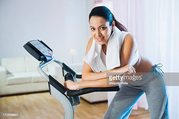 Woman leaning on a treadmill and smiling