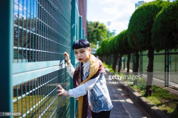 woman leaning on a wall - yusuke nishizawa stock pictures, royalty-free photos & images