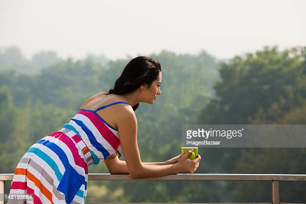 Woman leaning on balcony banister